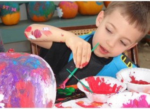 Max paints a pumpkin